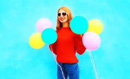 La fille drôle tient les ballons à air colorés sur le bleu Image stock