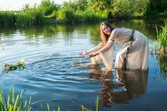 La fille drôle attirante abaisse la guirlande dans l'eau photo libre de droits