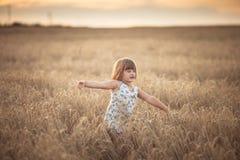 La fille drôle danse dans le domaine avec du seigle au coucher du soleil Photo libre de droits
