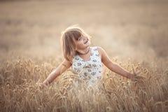 La fille drôle danse dans le domaine avec du seigle au coucher du soleil Photo stock