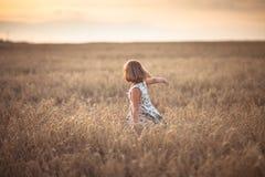 La fille drôle danse dans le domaine avec du seigle au coucher du soleil Image stock