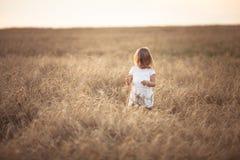 La fille drôle danse dans le domaine avec du seigle au coucher du soleil Images stock