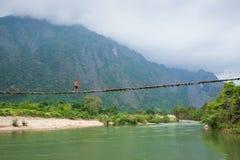 La fille du Laos dans l'habillement traditionnel de lao va sur un pont en bois OV Image stock