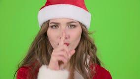 La fille du père noël dans le costume rouge dirige son doigt un peu plus tranquillement Écran vert Fin vers le haut banque de vidéos
