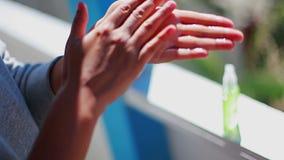 La fille effectue la désinfection de main utilisant une fiole antiseptique banque de vidéos