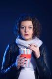 La fille a effrayé au cinéma, observant le film d'horreur photographie stock libre de droits