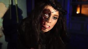 La fille effrayante de vampire avec le sang colle le couteau dans sa bouche banque de vidéos
