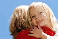 La fille embrassant la mère contre le ciel Images libres de droits