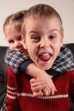 La fille embrasse le garçon pour le cou, Photo stock