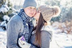 La fille embrasse son ami pour le présent le jour du ` s de Valentine Photographie stock