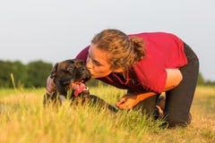 La fille embrasse son chien de boxeur Photos libres de droits