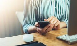 La fille employant le smartphone de doigt, le contact de femme au téléphone portable d'écran en atmosphère de local commercial ou Photographie stock libre de droits
