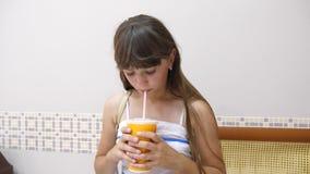 La fille en café boit un cocktail et un sourire délicieux banque de vidéos