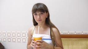 La fille en café boit un cocktail et un sourire délicieux clips vidéos