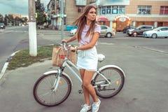La fille en carrefours de ville d'été, supports avec la bicyclette et paquet Attente d'une route libre pour aller Femme de concep images stock
