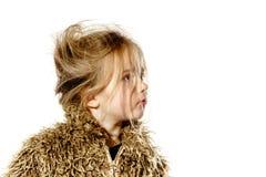 La fille en désordre d'élève du cours préparatoire avec de longs cheveux s'est habillée dans le manteau de fourrure Image libre de droits