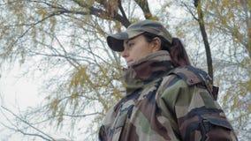 La fille en gros plan et belle de pêcheuse dans le costume de camouflage jette une canne à pêche dans la rivière dans un matin br banque de vidéos