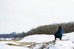 La fille en hiver s'assied sur une colline concept de l'attention ou de la tristesse image stock