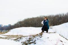 La fille en hiver s'assied sur une colline concept de l'attention ou de la tristesse photos stock