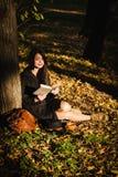 La fille en parc a lu le livre Photos stock
