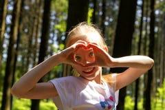 La fille en parc montre des mains de coeur Image stock