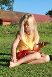La fille en rouge et le jaune rectifient se reposer avec de l'argent Images stock