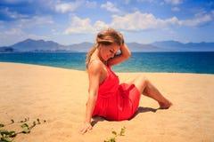 la fille en rouge s'assied sur des regards de cheveux de contacts de sable vers le bas contre la mer photos stock