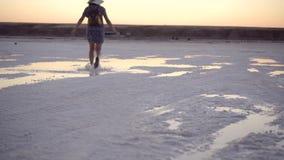 La fille en sandales vertes éclaboussent le saut par les magmas du lac de sel au temps de coucher du soleil banque de vidéos
