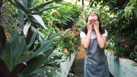 La fille en serre chaude dans le tablier, démangeant des usines de pollen Allergique aux fleurs clips vidéos