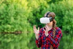 La fille en verres de réalité virtuelle tient ses mains devant elle, dans la perspective de la verdure Image libre de droits