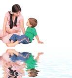 La fille enceinte avec l'enfant s'assied sur l'étage Images stock