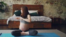 La fille enceinte convenable fait des exercices de sports se reposant sur le tapis de yoga sur le plancher de chambre à coucher e banque de vidéos