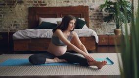 La fille enceinte gaie pratique le yoga faisant les courbures en avant à une jambe en position posée étirant le corps et les jamb banque de vidéos