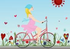 La fille enceinte monte une bicyclette sur le champ avec le fond de ciel bleu Photos libres de droits