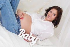 La fille enceinte tient le bébé en bois de lettres Image libre de droits