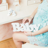 La fille enceinte tient le bébé en bois de lettres La femme enceinte dans une robe bleue s'assied près de sa coiffeuse Photographie stock libre de droits