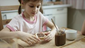 La fille enduit la pâte de chocolat sur un morceau de pain après que le dîner le mangent alors banque de vidéos