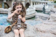 La fille enlève des verres de soleil se reposant sur une roche Photos stock