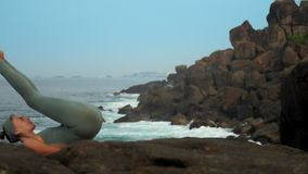 La fille entre dans le sarvangasana sur la pierre par mouvement lent d'océan banque de vidéos