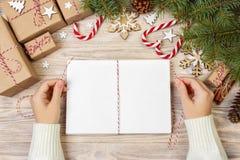 La fille enveloppe des lettres de Noël dans l'enveloppe, lettre du père noël d'enfants dans l'enveloppe, fond de Noël Images libres de droits