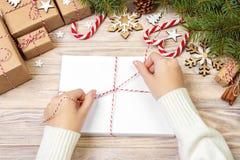 La fille enveloppe des lettres de Noël dans l'enveloppe, lettre du père noël d'enfants dans l'enveloppe, fond de Noël Photo libre de droits