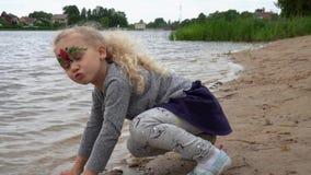 La fille espiègle 4 années s'asseyent par une eau de lac et le paiement avec le sable Mouvement de cardan clips vidéos