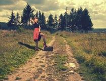 La fille essaye d'aller auto-stoppeur se tenant sur une route rurale Image stock