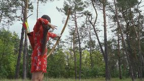 La fille essaye de frapper une flèche dans un arbre banque de vidéos