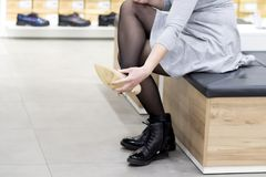 La fille essaye de nouvelles chaussures dans le magasin de chaussures la femme choisit des chaussures dans la boutique à la mode Images libres de droits