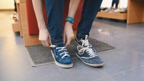 La fille essaye des espadrilles dans un magasin de chaussures - fin  Photographie stock libre de droits
