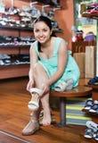 La fille essaye sur les sandales gîtées dans la boutique de chaussures Images stock