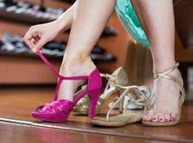 La fille essaye sur les sandales gîtées dans la boutique de chaussures Photo libre de droits