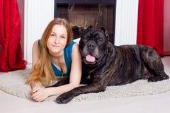 La fille est à la maison à côté de la cheminée avec son chien Cane Corso Photo stock