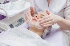 La fille est équipée de service de nettoyage de peau d'ultrason dans le salon de beauté photo libre de droits